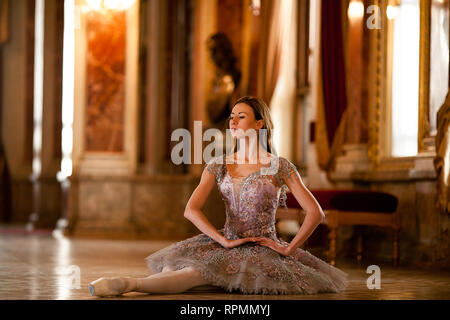 Beautiful ballerina dancing in a hall against the luxurious interior. - Stock Image