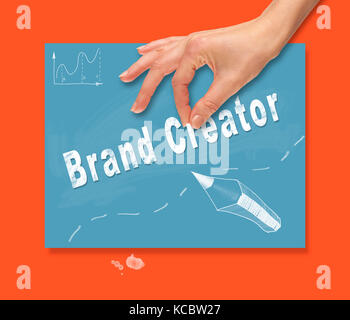 A hand picking up a Brand Creator concept on a colorful drawing board. - Stock Image