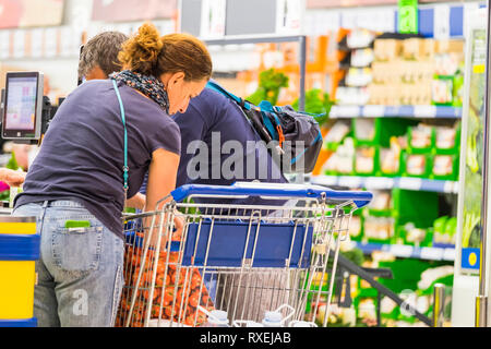 Couple of adult people family concept buying food and more at the mall market - daily life for usually people - Stock Image