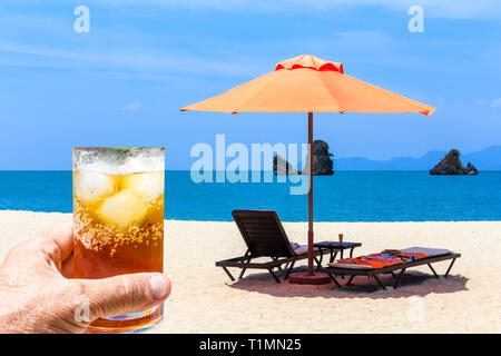 Hand holding glass of rum and coke with ice against sunloungers and a parasol on an empty Langkawi beach, Malaysia - Stock Image