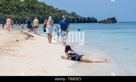 Enjoying the beach at West Bay Roatan Honduras people walk and lay in the sand. - Stock Image