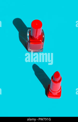Bottle with nail polish and red crimson lipstick on solid blue background. Bright sunlight strong shadows. Creative minimalist funky style pop art. Po - Stock Image