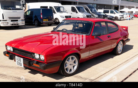 Three-quarters front view of a Red, 1984, Ford Capri, part of the 50th Anniversary celebrations at the 2019 Silverstone Classic Media Day - Stock Image