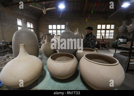 Jinhua, China's Zhejiang Province. 16th Feb, 2019. Chen Xinhua, the representative inheritor of Wuzhou kiln pottery firing, checks unglazed pottery wares at the workshop in Jinhua, east China's Zhejiang Province, Feb. 16, 2019. The first kiln of Wuzhou pottery wares were finished at the beginning of the Chinese Lunar New Year. The Wuzhou kiln pottery firing technique was listed as a national intangible cultural heritage in 2014. Credit: Xu Yu/Xinhua/Alamy Live News - Stock Image