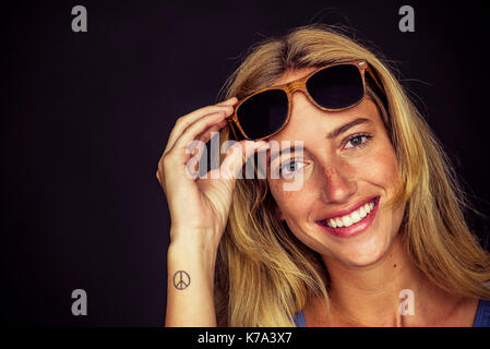 Young woman lifting sunglasses and smiling cheerfully at camera, portrait - Stock Image