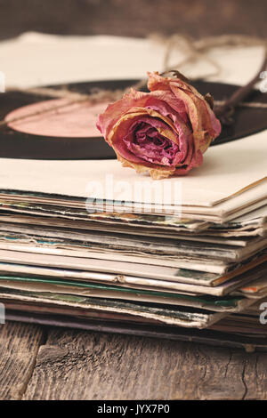 dry rose on a pile of old vinyl records in vintage style - Stock Image