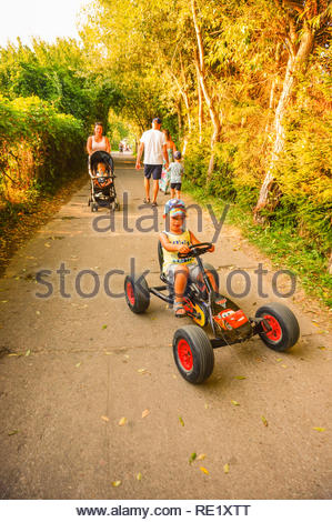 Sarbinowo, Poland - August 9, 2018: Boy riding a pedal go kart on a path with walking people on a sunny day by the seaside. - Stock Image