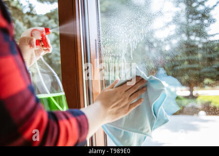 Woman is splashing cleaning liquid on the window with garden in the background. - Stock Image