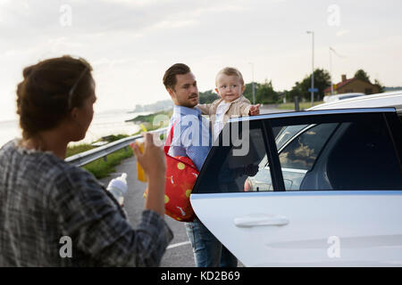 Father holding son (18-23 months) by car - Stock Image