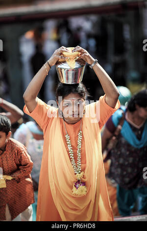 Woman holds milk pot on head during Thaipusam festival at Batu Caves in Selangor, Malaysia - Stock Image