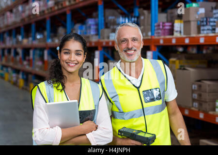 Portrait of warehouse workers standing with digital tablet and barcode scanner - Stock Image