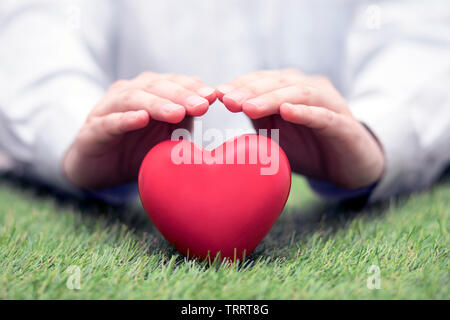 Red heart on green grass covered by hands. Health insurance or love concept - Stock Image