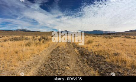Overview of dirt road crossing hIgh desert in Nevada, USA, with mountains in the background and partly cloudy skies - Stock Image