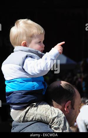 little boy sitting on father's shoulders, England, UK - Stock Image