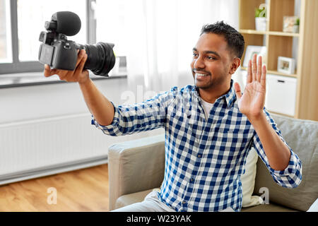 male video blogger with camera blogging at home - Stock Image