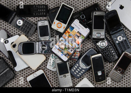 A modern smartphone on a pile of old, obsolete mobile phones. - Stock Image
