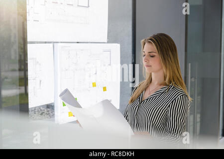 Woman contemplating plans on glass wall - Stock Image