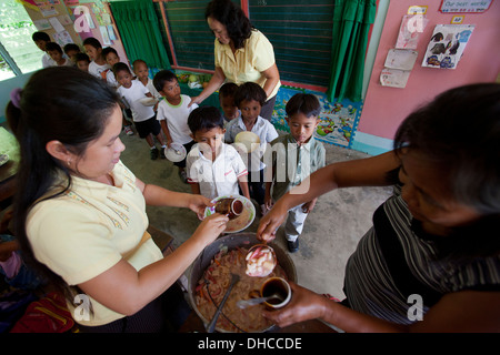 Children wait for a free lunch during a feeding program event at Wasig Elementary School in Wasig, Oriental Mindoro, Philippines - Stock Image