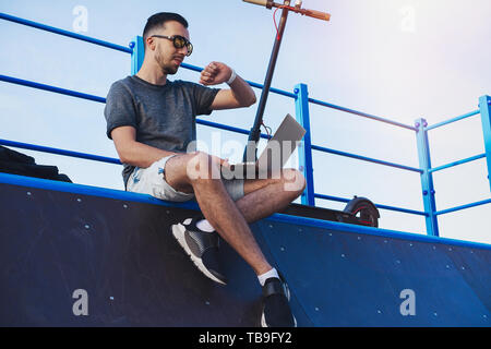 Young attractive man with laptop and modern electric kick scooter sitting at skater ramp in contemporary park. and working Freelancer or business man  - Stock Image