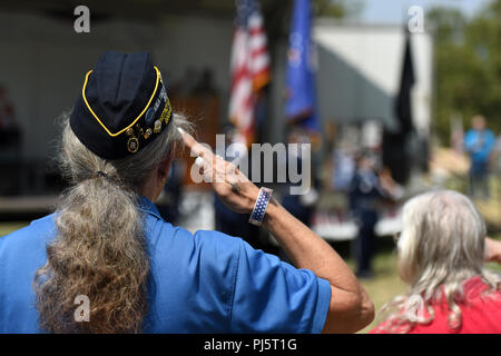 Cynthia Verrill, Linda American Legion Post 807 commander, salutes the flag during the playing of the National Anthem during the Yuba-Sutter Stand Down Aug. 24, 2018, in Marysville, California.The Stand Down gives local veterans and their families the opportunity to seek services, such as dental, veteran benifits and social security, in a sigle location. (U.S. Air Force photo by Staff Sgt. Ramon A. Adelan) - Stock Image
