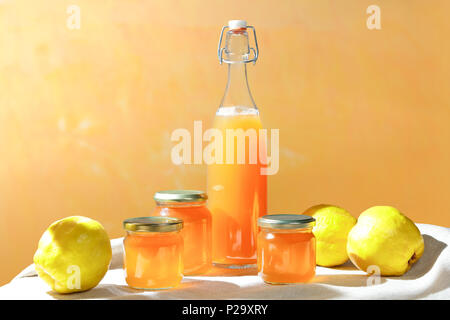 Homemade quince jelly and Juice in a bottle and glass jars with quinces on a linen tablecloth in bright sunshine in front of an yellow and orange background - Stock Image