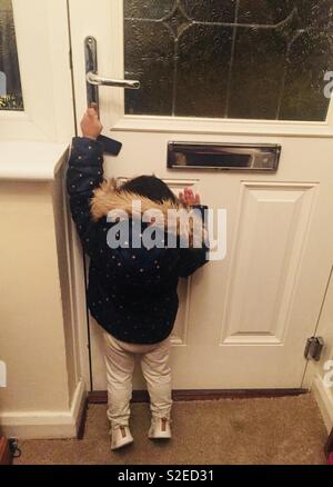 A toddler trying to reach a door handle to open the front door - Stock Image