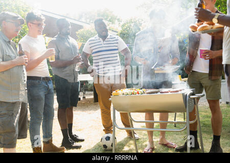 Male friends drinking beer and barbecuing in sunny summer backyard - Stock Image