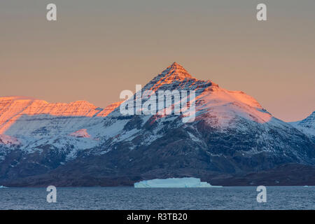 Greenland. Scoresby Sund. Gasefjord (Gooseford) Alpenglow on the mountain with iceberg. - Stock Image