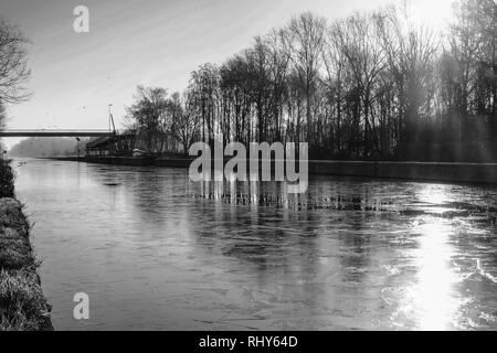 Dramatic and monochrome sunrise over a Beautiful early winter landscape with a frozen river or canal, treelined riverside and grass at sunrise creatin - Stock Image