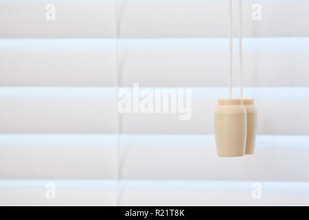 A string for pulling a blind open and closed beside a drawn shutter - Stock Image