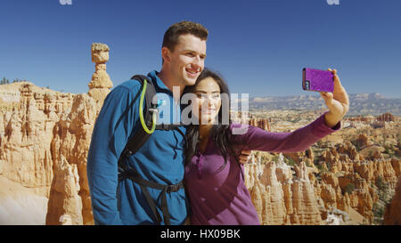 Boyfriend and girlfriend taking selfie with smartphone near scenic rock formations in remote landscape under clear - Stock Image