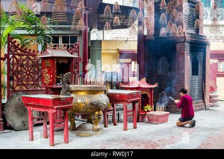 Sin Sze Si Ya Taoist Temple, Chinatown, Kuala Lumpur, Malaysia.  Worshiper Kneeling with Joss (Incense) Sticks in front of Shrine. - Stock Image