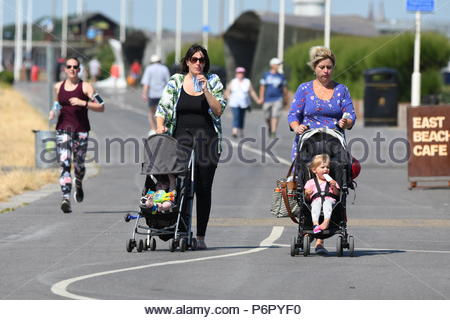 Littlehampton, UK. Monday 2nd July 2018. Women with pushchairs on the seafront promenade on another very warm and humid morning in Littlehampton, on the South Coast. Credit: Geoff Smith / Alamy Live News. - Stock Image
