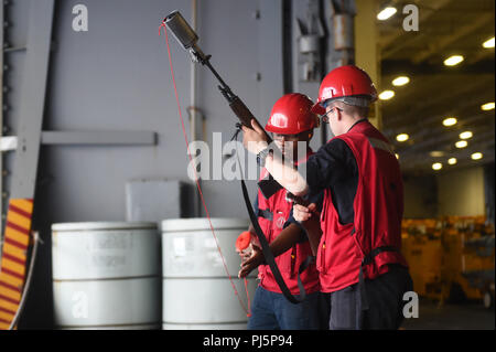 180824-N-JX484-008  ATLANTIC OCEAN (Aug. 24, 2018)  Gunner's Mate 2nd Class Marquese Richardson (left) and Gunner's Mate Seaman Halden Pettit prepare to fire a shot line during a replenishment-at-sea in the hangar bay of the Nimitz-class aircraft carrier USS Abraham Lincoln (CVN 72) in preparation for a replenishment-at-sea.  Abraham Lincoln is currently underway conducting carrier qualifications. (U.S. Navy photo by Mass Communication Specialist 2nd Class Mark Andrew Hays/Released) - Stock Image