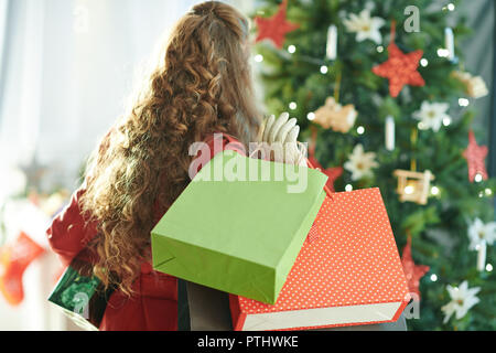 Seen from behind modern woman in red trench coat with shopping bags and Christmas present box near Christmas tree - Stock Image