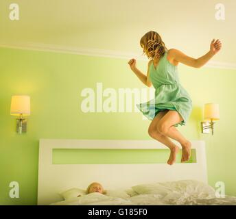 Mother jumping on bed to wake sleeping son - Stock Image