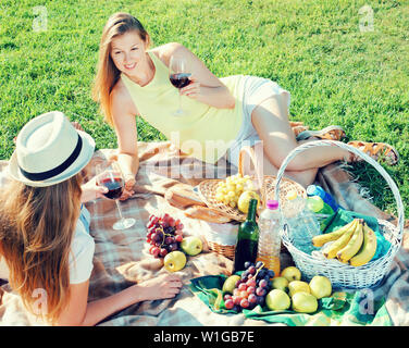 Happy cheerful positive girl enjoying conversation with her friend on picnic outdoors - Stock Image