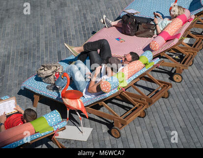 People relaxing on reclining deckchairs in summer sunshine, London, UK - Stock Image