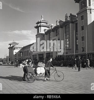 1950s, Beijing, China, Father with his childrem and luggage, pushes his large tricycle across a public square infront of a large buidling with a picture of Chiarman Mao outside it. - Stock Image