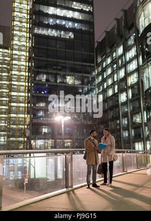Businessmen discussion paperwork on urban pedestrian bridge at night - Stock Image