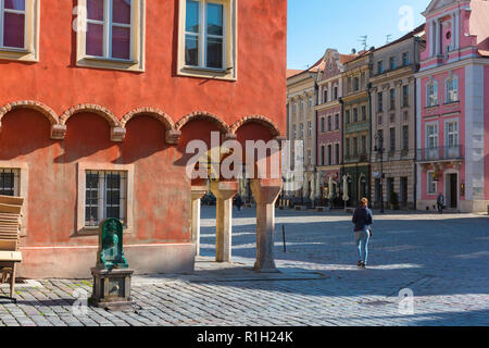 Poznan Market Square, view of a young woman walking through the colorful Market Square in Poznan Old Town on a summer morning, Poland. - Stock Image