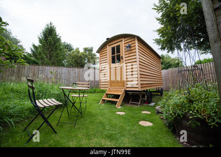 Hand built wooden shepherds' hut in a rural garden with a table and chairs    ready for holiday guests looking for cosy glamping in Suffolk, UK - Stock Image