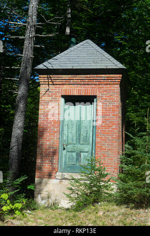 Little brick pump house alongside a carriage road in Acadia National Park, Maine, USA. - Stock Image