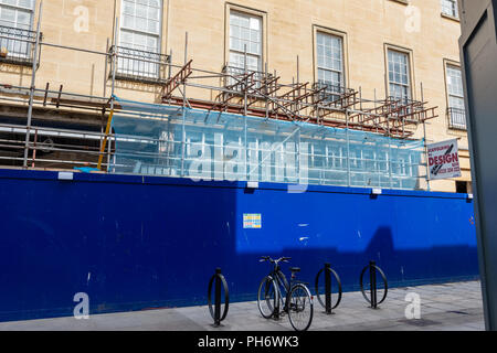 A building  with scaffolding and a wooden security fence on the ground floor  with a pushbike and bike storage in front of it - Stock Image