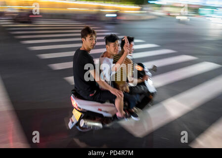 Three teen boys wave while pass by on motor scooter speed through city center on hot summer night, Libo, Guizhou Province, China. - Stock Image