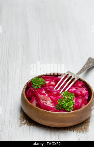 Salad  with cabbage and beetroot in wooden bowl on white table - Stock Image