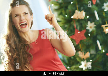 smiling trendy woman in red dress near Christmas tree got idea - Stock Image