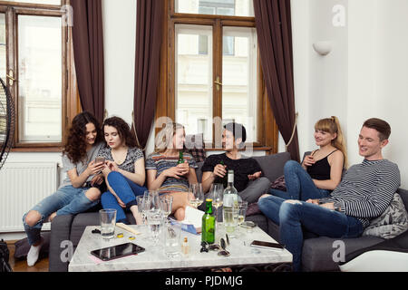 Group of male and female adult friends sitting on sofa chatting and drinking - Stock Image