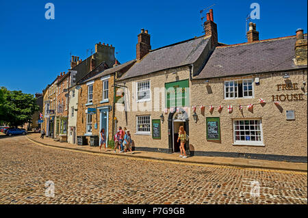 The Unicorn public house and ornate buildings line a cobbled street in  the North Yorkshire market town of Richmond. - Stock Image