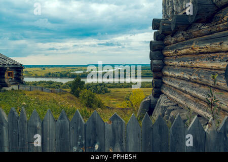 Wooden fence with pointed ends with a log cabin against the background of a river - Stock Image